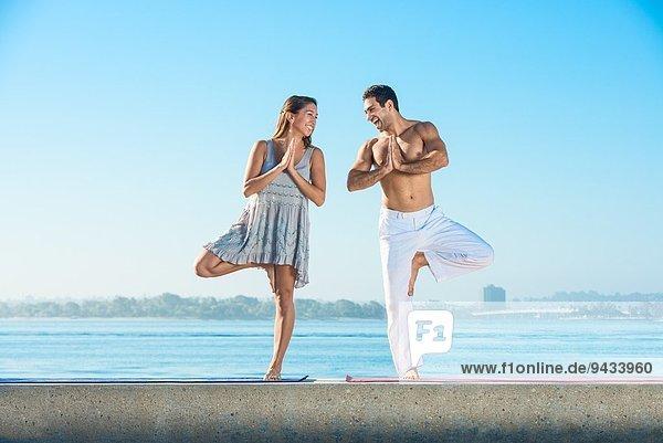 Junger Mann und junge Frau beim Yoga am Pier am Pacific Beach  San Diego  Kalifornien  USA