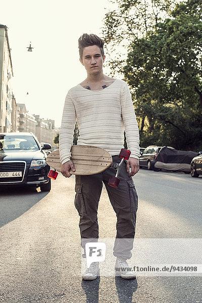 Ganzkörperporträt selbstbewusster männlicher Gymnasiast mit Skateboard auf der Stadtstraße