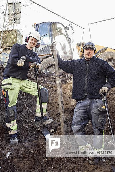 Porträt der selbstbewussten Bauarbeiter auf der Baustelle