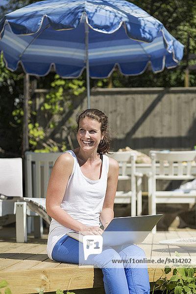 Fröhliche mittlere erwachsene Frau mit Laptop zum Entspannen auf der Terrasse