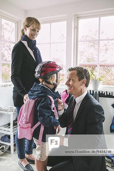 Geschäftsmann  der die Tochter anzieht  während die Frau sie ansieht.