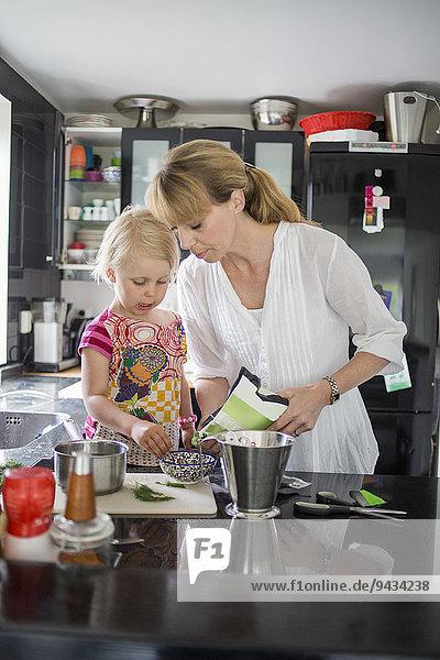 Mutter und Tochter bei der Zubereitung von Speisen in der Küche