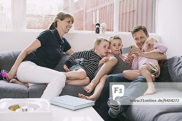Familie mit Smartphone auf dem Sofa zu Hause