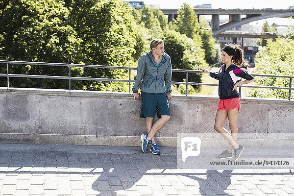 Volle Länge des passenden Paares  das sich auf der Brücke unterhält
