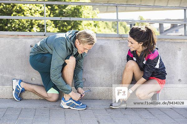 Lächelndes Paar mit Schnürsenkeln vor dem Joggen auf der Brücke