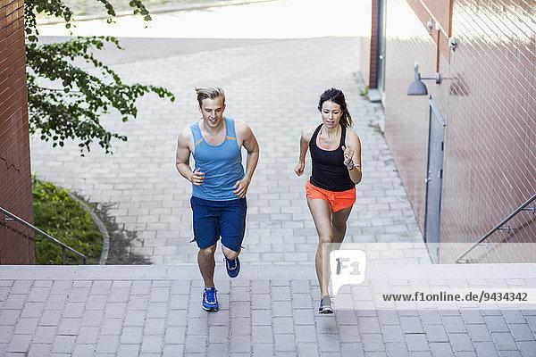 Volle Länge des Paares  das auf Stufen im Freien läuft