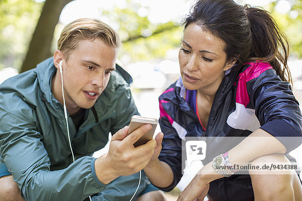 Fit couple using mobile phone at park