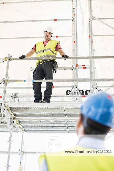 Rear view of architect looking at construction worker standing by railing