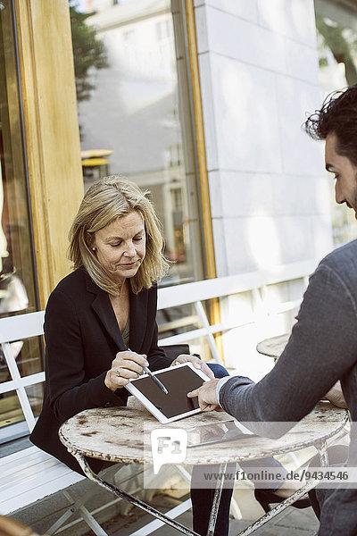 Geschäftskollegen mit digitalem Tablett im Straßencafé