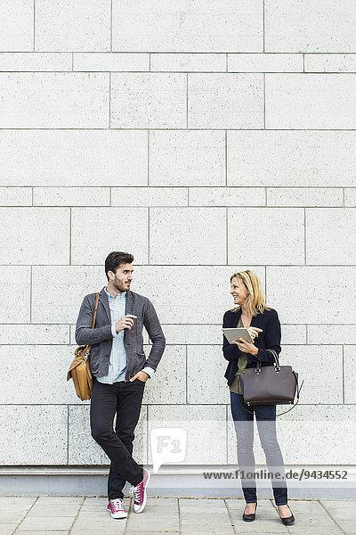 Volle Länge von lächelnden Geschäftsleuten  die auf dem Bürgersteig diskutieren.