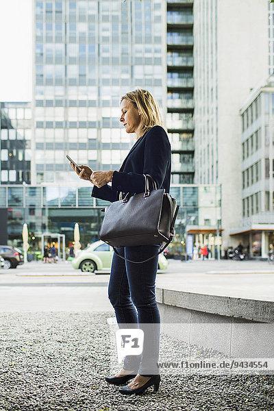 Durchgehende Seitenansicht der Geschäftsfrau mit dem Handy auf dem Bürgersteig der Stadt