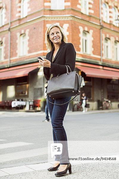 Volle Länge der lächelnden Geschäftsfrau  die weg schaut  während sie das Handy auf der Straße benutzt.