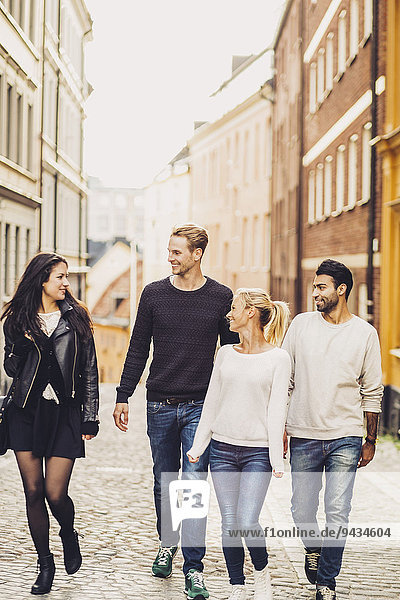 Multikulturelle Freunde  die auf der Straße spazieren gehen.