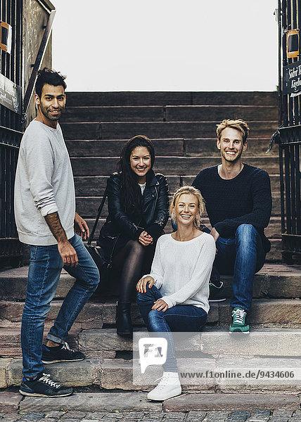 Porträt von glücklichen multiethnischen Freunden auf Stufen