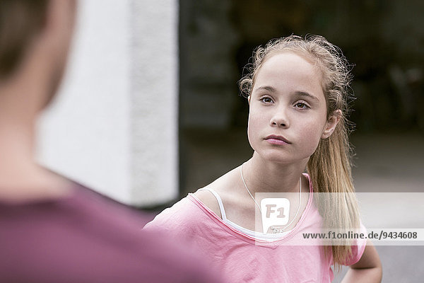 Angry girl looking at father outdoors