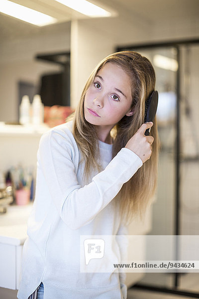Girl combing hair at home