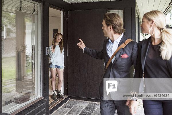 Eltern unterrichten die Tochter beim Verlassen des Hauses