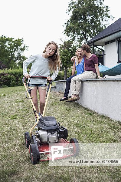 Mädchen beim Rasenmähen mit Eltern  die im Hintergrund auf dem Hof sitzen