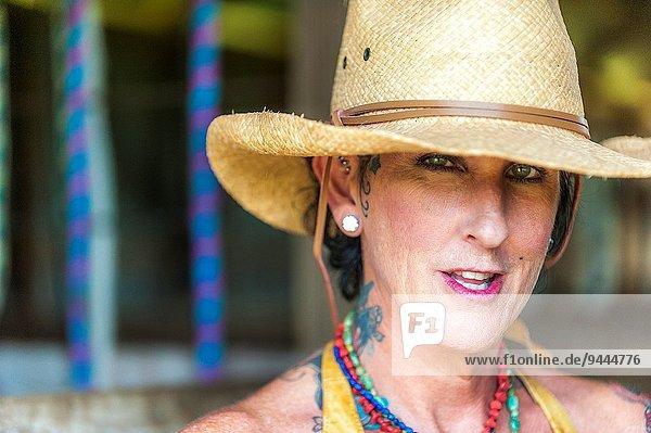 Frau sehen Tischset Hut braunhaarig Tätowierung Blick in die Kamera Kleidung Strohhut Außenaufnahme Stroh alt Jahr