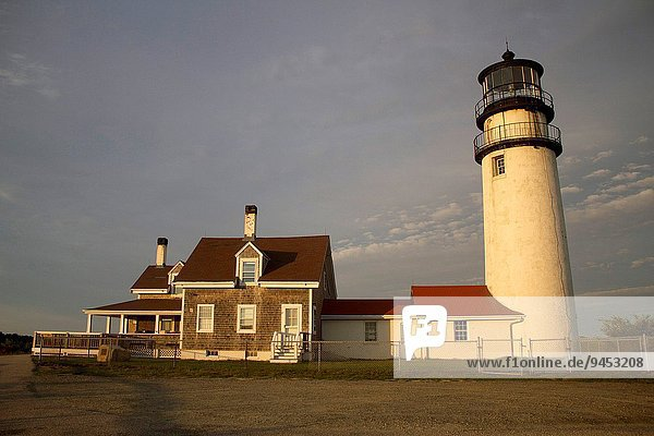 Sunset on a Cape Cod house and lighthouse outside of Sandy Town in Cape Cod  Massachusetts.Typical Cape Cod house. Landscape in the town of Cape Cod.