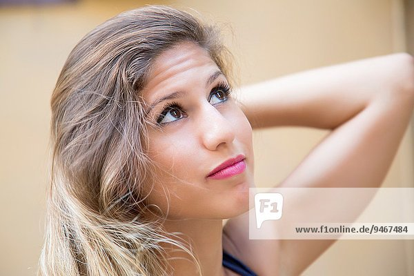 Beautiful young woman looking up.