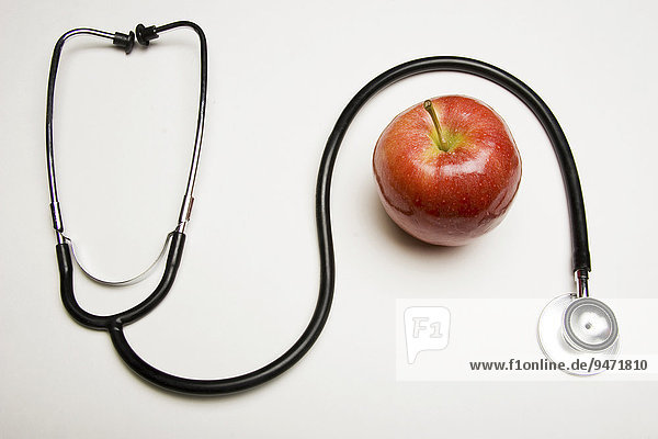 Stethoscope and red apple  concept: An apple a day keeps the doctor away