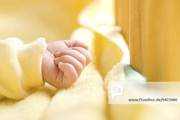 Geballte Babyhand in einem Kinderbett Geballte Babyhand in einem Kinderbett