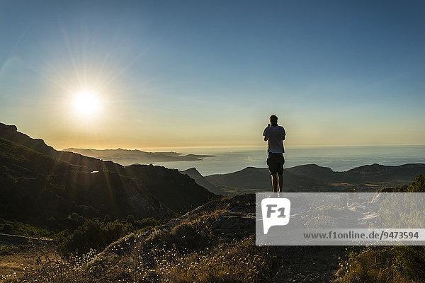 Junger Mann fotografiert Sonnenuntergang  Abendrot am Meer  Golf von Saint-Florent  Korsika  Frankreich  Europa