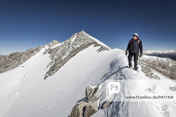 Bergsteiger beim Aufstieg zum Hohen Weißzint  hier am Gipfelgrat  hinten der Gipfel mit Kreuz  an der Landesgrenze  Zillertaler Alpen  Lappach  Mühlwaldertal  Tauferer Ahrntal  Pustertal  Südtirol  Italien  Alpen  Finkenberg  Tirol  Österreich  Europa