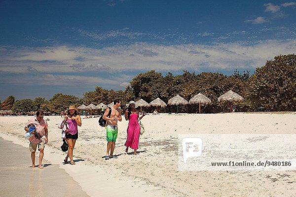 Tourists walking on the sandy Ancon beach  Trinidad  Sancti Spiritu Province  Cuba  West Indies  Central America.