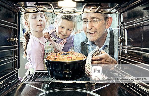 Mann und zwei Mädchen beim Kuchenbacken aus der Innenperspektive des Backofens