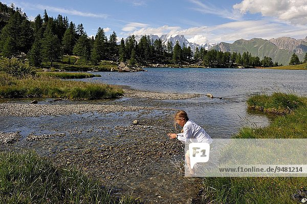 little girl walking on the bank of the mountain lake Arpy,  near La Thuile,  Aosta Valley,  Italy,  Europe.