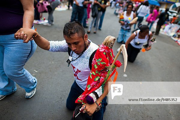 A Mexican follower of Santa Muerte (Saint Death)  holding a sacred figurine  makes the pilgrimage on his knees in Tepito  a rough neighborhood of Mexico City  Mexico  1 May 2011. The religious cult of Santa Muerte is a syncretic fusion of Aztec death worship rituals and Catholic beliefs. Born in lower-class neighborhoods of Mexico City  it has always been closely associated with crime. In the past decades  original Santa Muerte's followers (such as prostitutes  pickpockets and street drug traffickers) have merged with thousands of ordinary Mexican Catholics. The Saint Death veneration  offering a spiritual way out of hardship in the modern society  has rapidly expanded. Although the Catholic Church considers the Santa Muerte's followers as devil worshippers  on the first day of every month  crowds of believers in Saint Death fill the streets of Tepito. Holding skeletal figurines of Holy Death clothed in a long robe  they pray for power healing  protection and favors and make petitions to 'La Santísima Muerte'  who reputedly can make life-saving miracles.