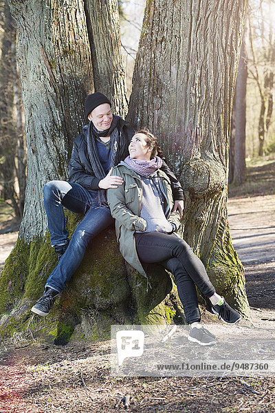 Happy young couple sitting by a tree  Sweden  Europe
