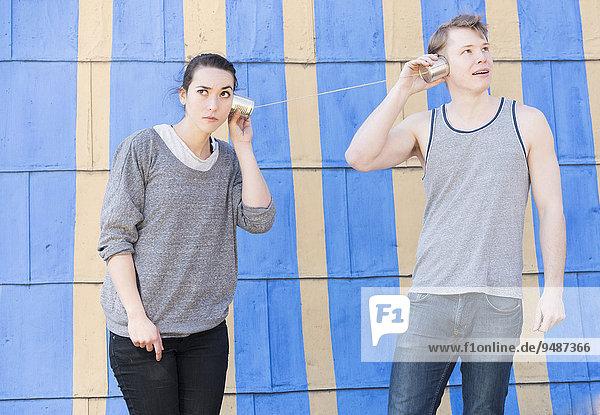 Junge Frau und junger Mann mit einem Dosentelefon  beide hören zu  Symbolbild  Kommunikation in einer Beziehung