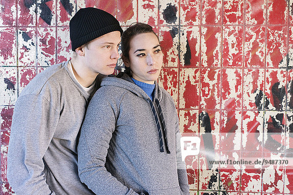 Casual and relaxed young man and woman waiting in front of grafitti wall in urban area  Sweden  Europe
