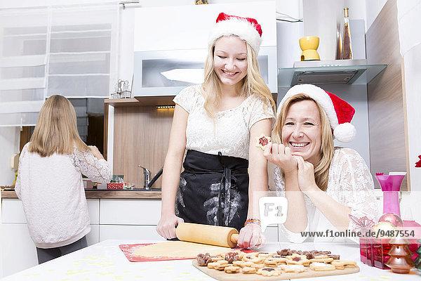 Mutter und Töchter in der Küche  beim Backen von Weihnachtsplätzchen