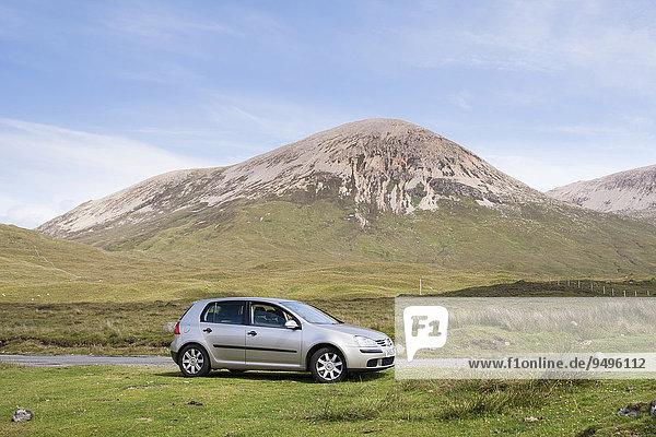 Volkswagen Golf Auto neben der Straße geparkt  mit dem Berg Beinn Dearg hinten  Strathaird  Isle of Skye  Schottland  Großbritannien  Europa