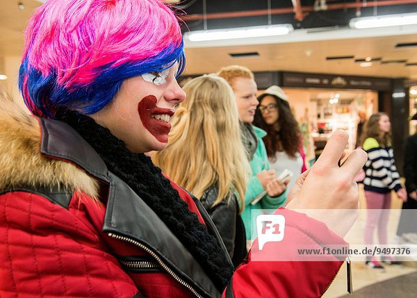 Utrecht  Netherlands. Feale mime player with a painted face in a shopping mall  just prior to her public performance.