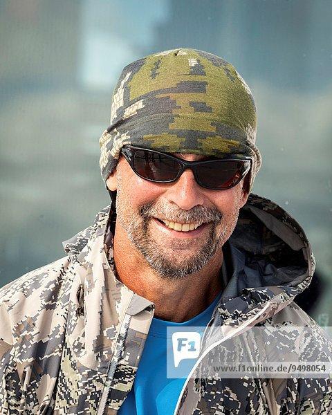 Mann lächeln Tarnung Hut Jacke Kleidung Sonnenbrille