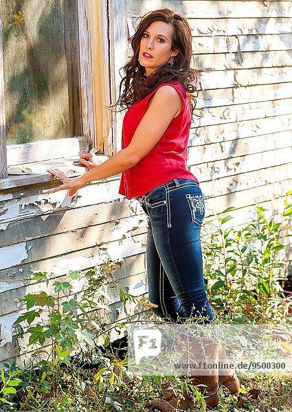 Außenaufnahme stehend Gesichtsausdruck Gesichtsausdrücke Ausdruck Ausdrücke Mimik Frau ernst sehen Wohnhaus braunhaarig Blick in die Kamera gerade alt freie Natur Jahr