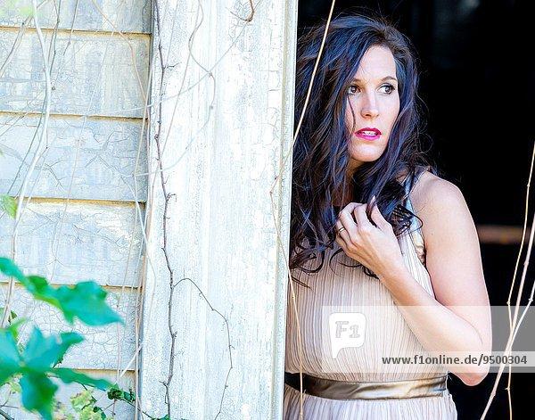 Außenaufnahme stehend Frau sehen Wohnhaus Eingang braunhaarig Blick in die Kamera wegsehen Reise alt freie Natur Jahr