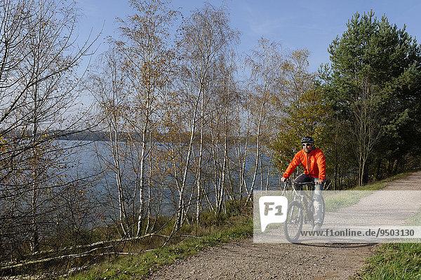 Cyclist  bicycle tour at Murner See lake  Upper Palatinate Lakeland  near Wackersdorf  Upper Palatinate  Bavaria  Germany  Europe