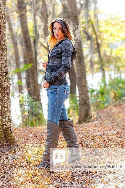 Außenaufnahme Frau sehen gehen über Weg Stiefel Pullover hoch oben braunhaarig Herbst blau Jeans Blick in die Kamera Kleidung 30 alt freie Natur Jahr