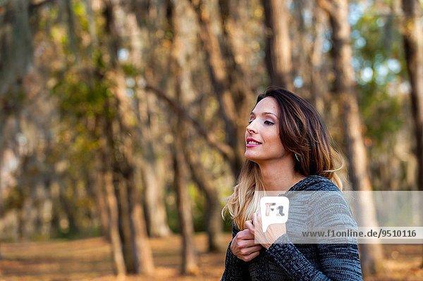 Frau sehen Baum Pullover Hintergrund braunhaarig Herbst Blick in die Kamera wegsehen Reise Kleidung 30 alt Jahr