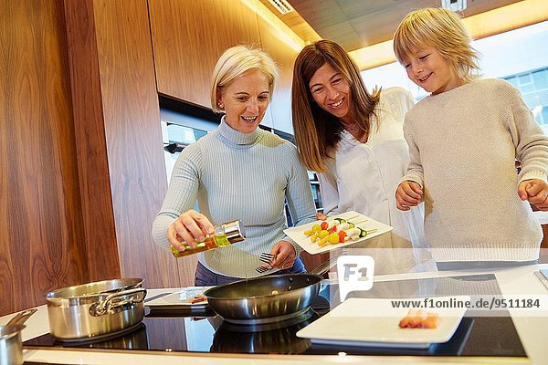 Family in the kitchen. Three generations. Healthy eating. Healthy growth. Cooking fish and vegetable skewer.