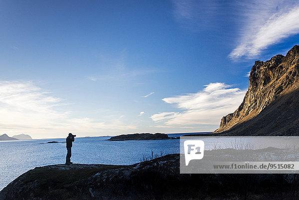 Fotograf auf einem Felsen  Tangstad  Lofoten  Norwegen  Europa