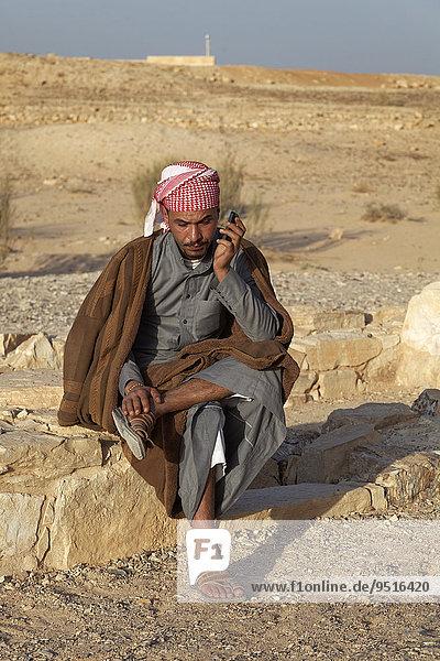 Jordanier in traditioneller Kleidung telefoniert mit Mobiltelefon  Wüstenschloss Qusair 'Amra oder Qusaie Amra  Jordanien  Asien