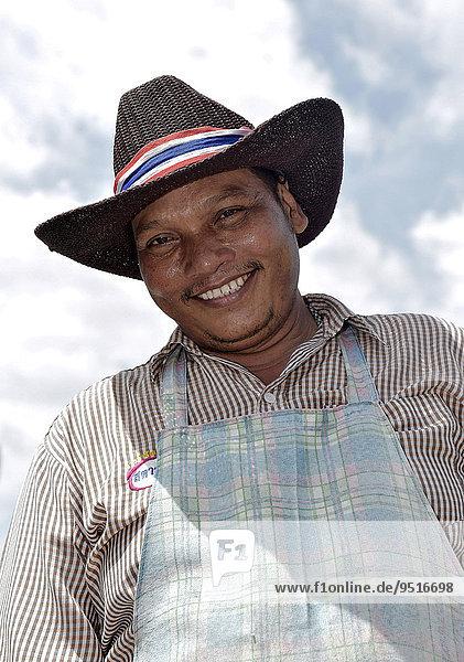 Lachender Mann mit Hut und Schürze  Hua Hin  Thailand  Asien