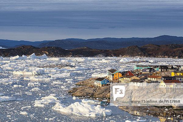 Bunte Holzhäuser am Meer mit Bruchstücken eines Eisbergs  Ilulissat  Grönland